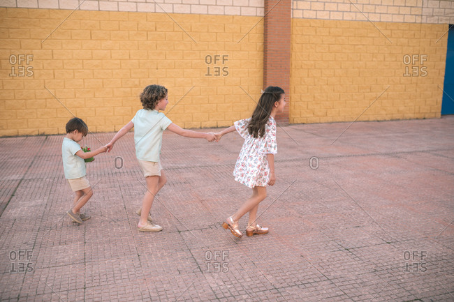 Three siblings holding hands and walking in the street