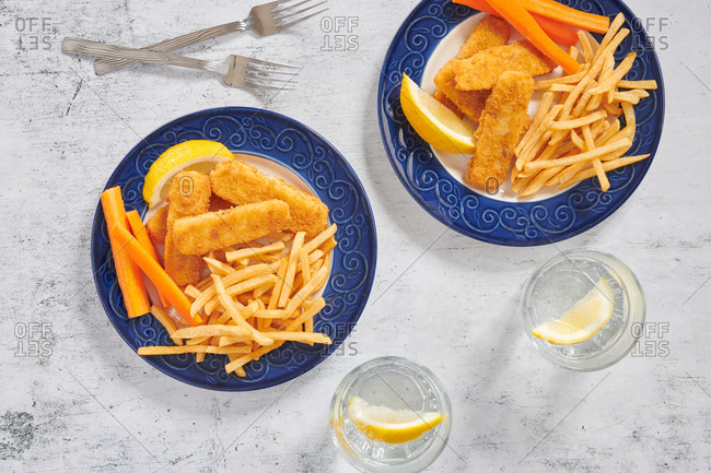 Fish sticks and French fries served with carrot sticks