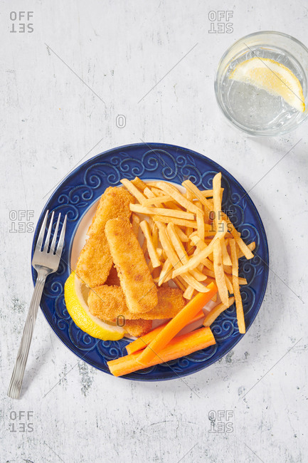 Fish sticks and French fries served with carrot sticks.