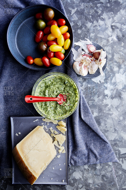 Fresh herb dip with tomatoes and garlic and parmesan on a blue metal surface with a blue linen cloth,