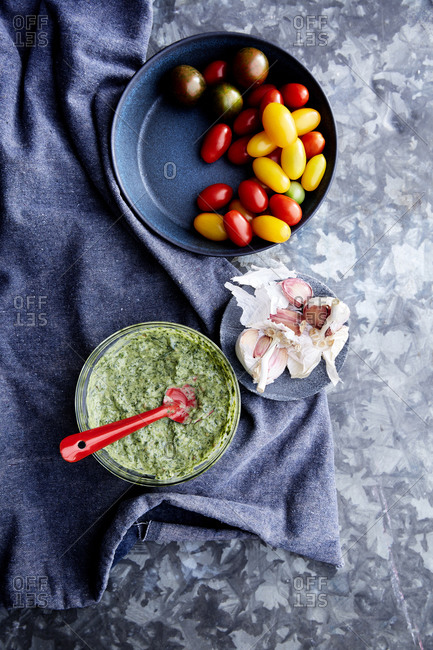 Fresh herb dip with tomatoes and garlic on a blue metal surface with a blue linen cloth,