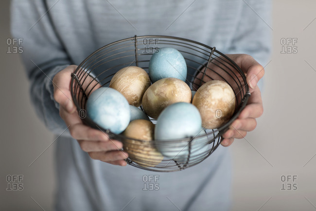 Hands holding colored eggs in wire basket