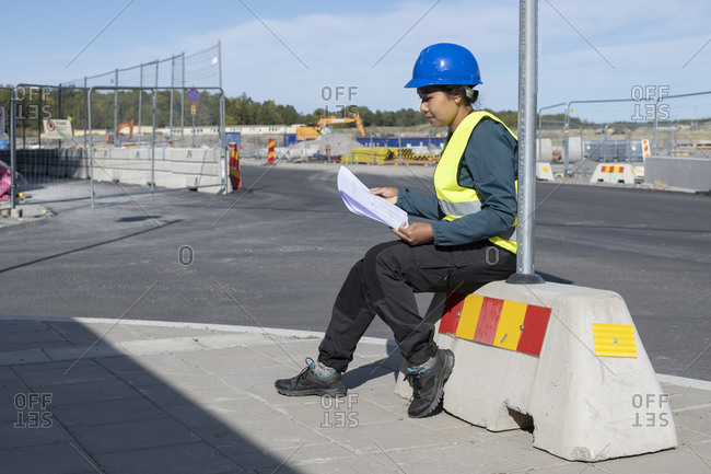 Woman holding blueprint at construction site