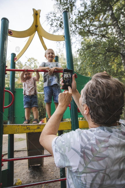 Father taking picture of kids at playground