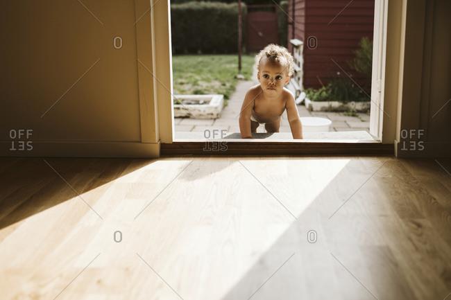 Toddler crawling through door - Offset