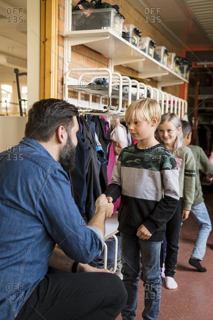 Teacher greeting children