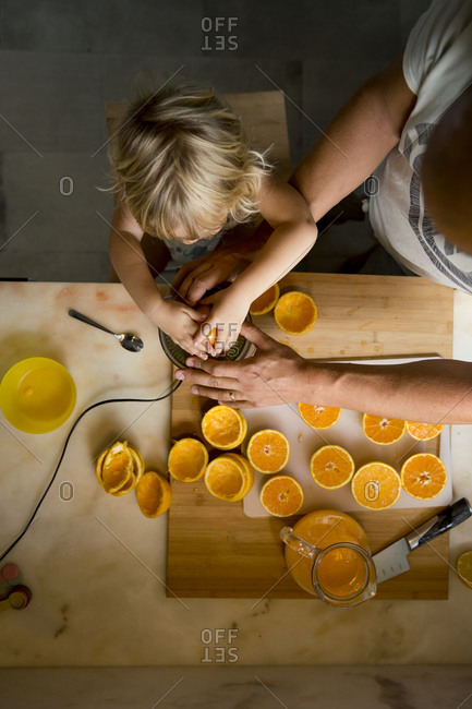 Boy making orange juice with father