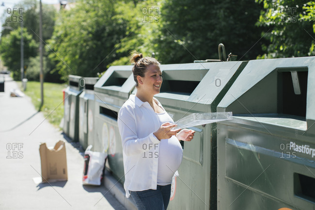 Pregnant woman recycling plastic outdoors