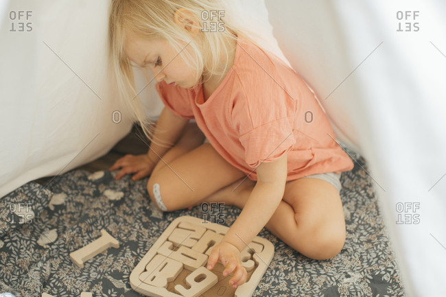 Girl solving wooden puzzles