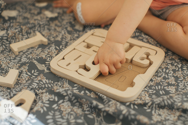 Child solving wooden puzzles