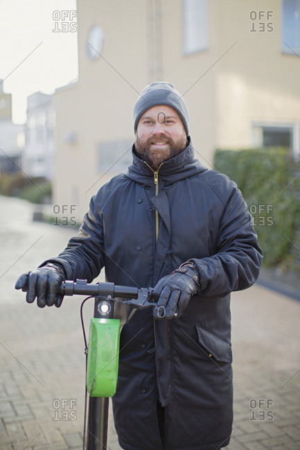 Man holding electric scooter - Offset