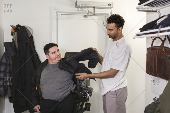 Career helping man in wheelchair putting jacket on