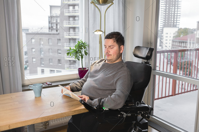 Man on wheelchair reading at table