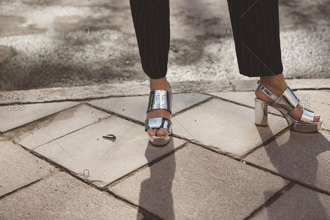Woman wearing silver sandals, low section