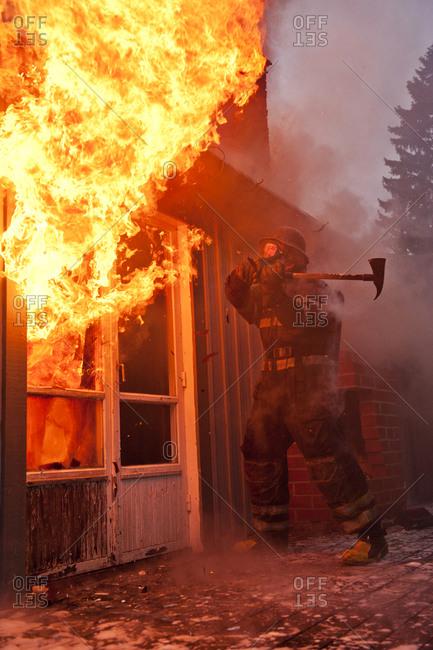 Fireman entering burning house