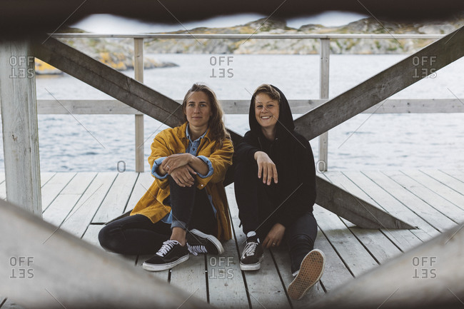 Smiling women sitting on jetty