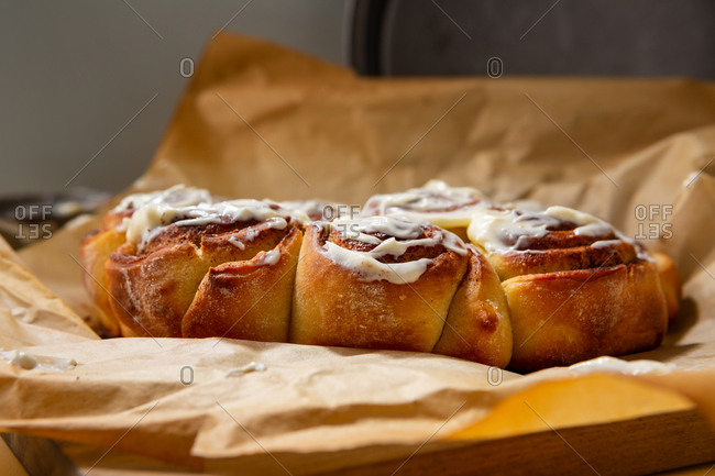 Close up view of cinnamon buns drizzled with frosting
