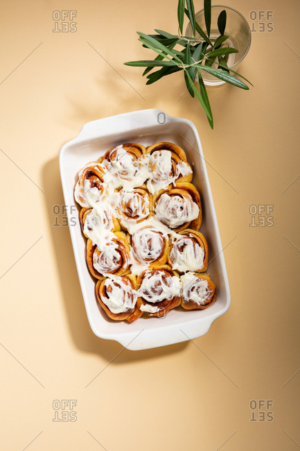 Overhead view of buns in baking dish on a beige background