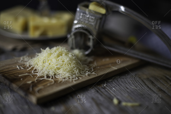 Grated gruyere cheese with vintage grater on a wooden cutting board