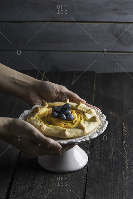 Hands holding rustic mango galette with blueberries and cinnamon on a wooden background