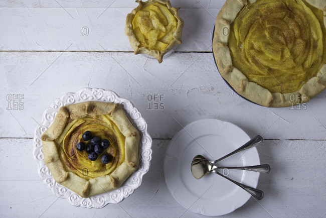 Assortment of rustic mango galettes with cinnamon and blueberries on a white wooden background
