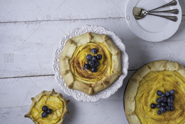 Assortment of rustic mango galettes with cinnamon and blueberries