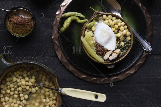 Tunisian chickpeas dish prepared with bread, tuna, and poached egg