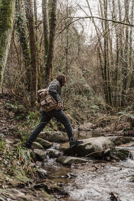 young man with backpack- crossing steam in forest