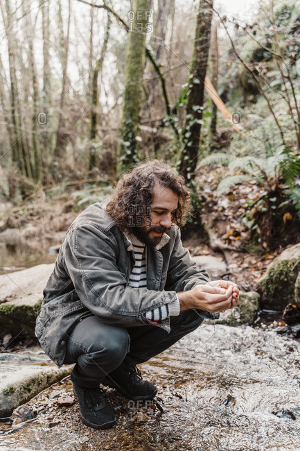 Young man crouching at stream in forest- drinking water from cupped hands