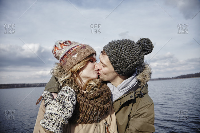 Young couple kissing in front of a lake