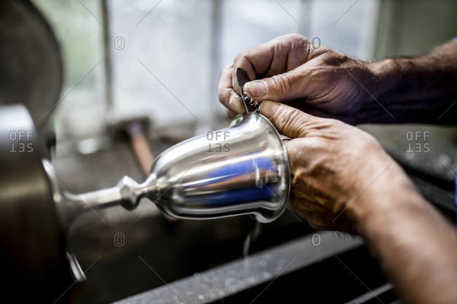 Austria- Hands of male metal worker manufacturing tin chalice in foundry