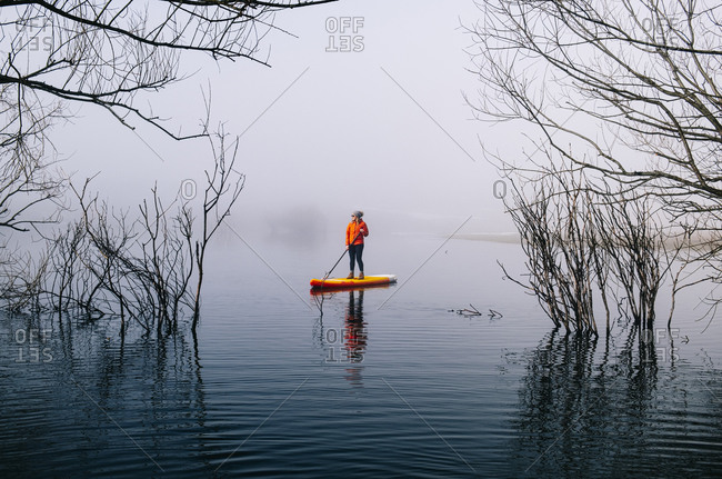 Woman stand up paddle surfing on a lake in the fog