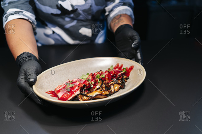 Chef showing prepared dish on table in restaurant kitchen