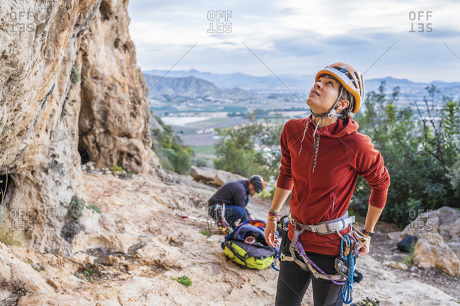 Female climber preparing looking up rock face