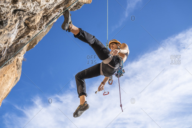 Female climber abseiling from rock face