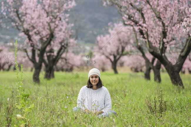 Portrait of teenage girl sitting on a meadow in front of blossoming almond trees