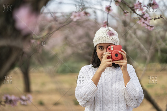Portrait of teenage girl taking photo with camera among blossoming almond trees