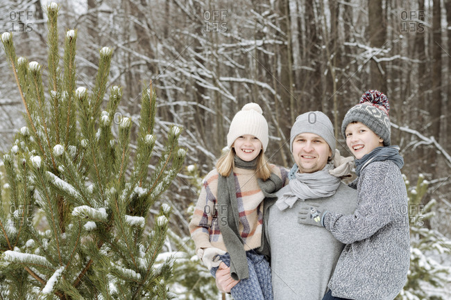 Portrait of happy father with two children at a fir tree in winter