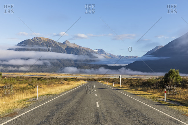 New Zealand- Fog floating over empty State Highway 73 with mountains in background