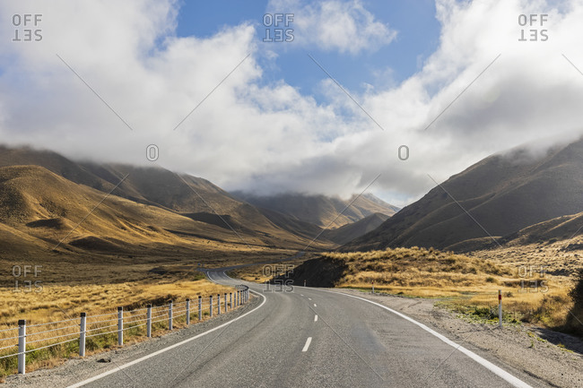New Zealand- Clouds over empty State Highway 8 in Lindis Pass