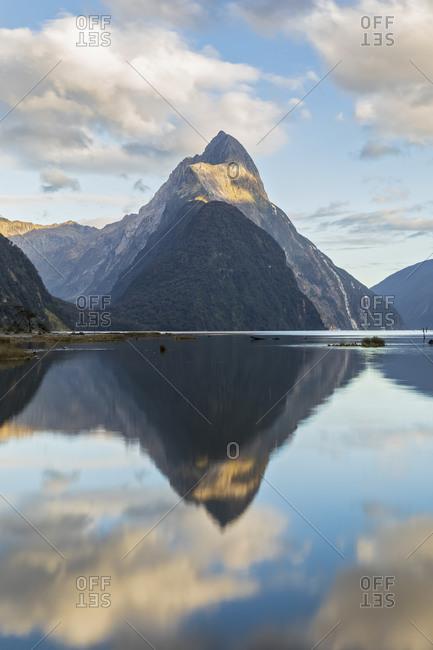 New Zealand- Mitre Peak reflecting on shiny surface of Milford Sound
