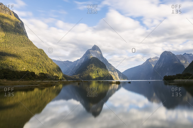 New Zealand- Scenic view of clouds and mountains reflecting on shiny surface of Milford Sound