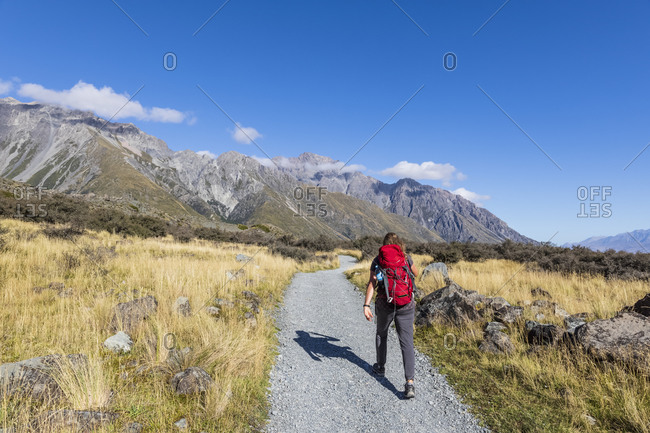 New Zealand- Oceania- South Island- Canterbury- Ben Ohau- Southern Alps (New Zealand Alps)- Mount Cook National Park- Tasman Glacier Viewpoint- Rear view of woman hiking