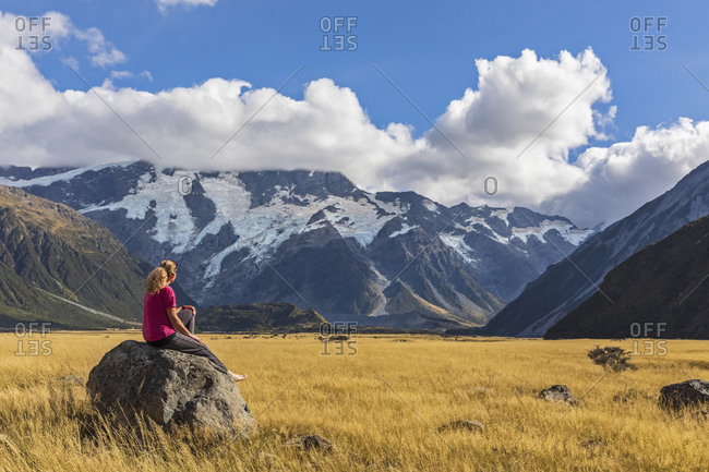 New Zealand- Oceania- South Island- Canterbury- Ben Ohau- Southern Alps (New Zealand Alps)- Mount Cook National Park- Aoraki / Mount Cook- Woman sitting on boulder in mountain landscape