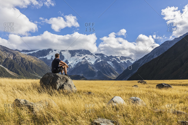 New Zealand- Oceania- South Island- Canterbury- Ben Ohau- Southern Alps (New Zealand Alps)- Mount Cook National Park- Aoraki / Mount Cook- Man sitting on boulder in mountain landscape