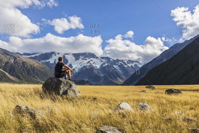 New Zealand- Oceania- South Island- Canterbury- Ben Ohau- Southern Alps (New Zealand Alps)- Mount Cook National Park- Aoraki / Mount Cook- Man sitting on boulder in mountain landscape
