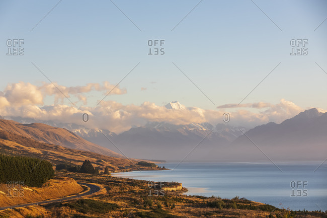 New Zealand- Scenic view of New Zealand State Highway 80 stretching along shore of Lake Pukaki at dawn with Mount Cook in background