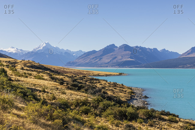 New Zealand- Clear sky over turquoise shore of Lake Pukaki with Mount Cook looming in background