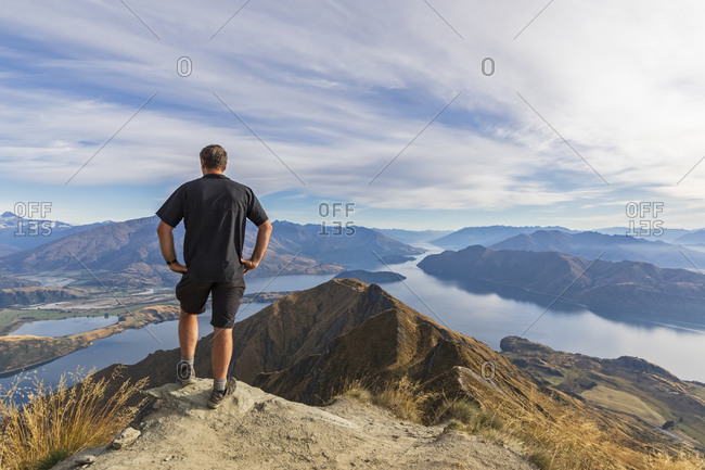 Hiker standing on viewpoint at Roys Peak- looking to Mount Aspiring- Lake Wanaka- South Island- New Zealand