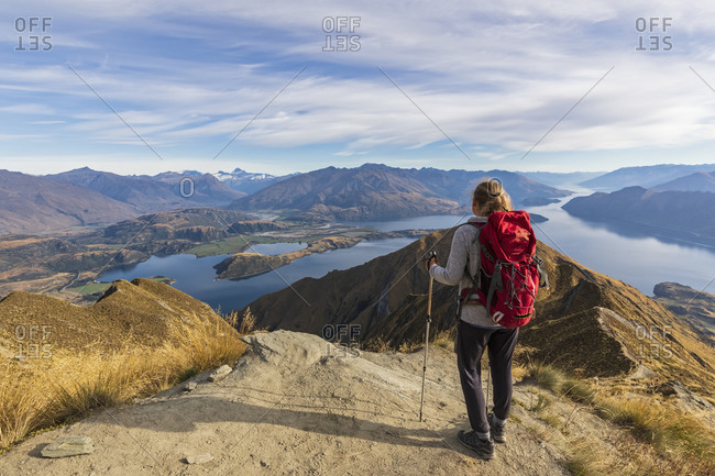 Woman standing on viewpoint at Roys Peak- looking to Mount Aspiring- Lake Wanaka- South Island- New Zealand